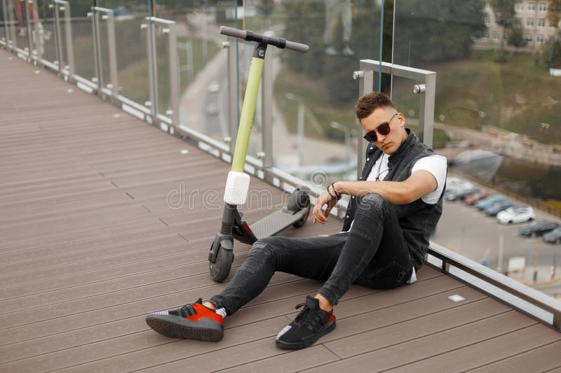 Young urban guy in fashionable gray jeans clothes in trendy black sunglasses sits next to an electric scooter on a wooden floor stock images