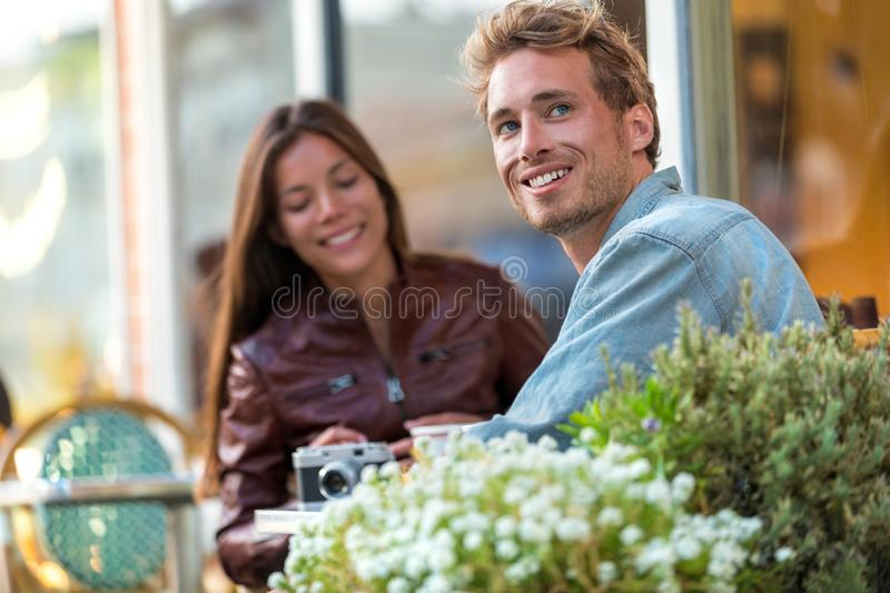 Young urban man enjoying sitting at restaurant table with friend in city. European travel couple vacation. Casual lifestyle royalty free stock photography