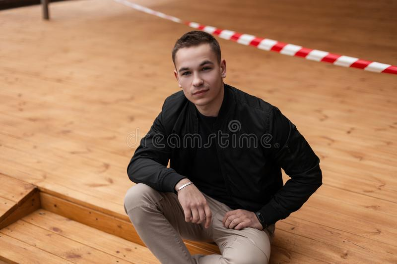 Young urban modern man in a fashionable black spring jacket in stylish beige trousers with a trendy hairstyle poses sitting. On a wooden terrace of a summer royalty free stock photography