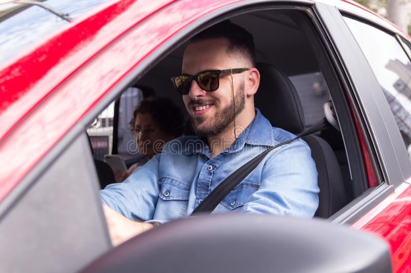 Young professional driver taking passenger to ride in private vehicle. Concept of commute, transport service, mobility. Young urban professional driver wearing stock photo
