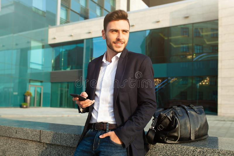 Young urban professional man using smart phone. Businessman holding mobile smartphone using app texting sms message wearing jacket royalty free stock images