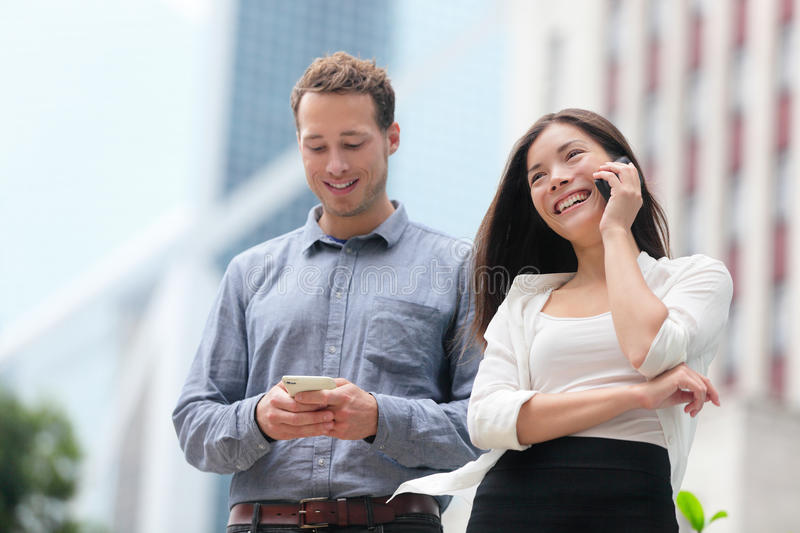Young urban professionals business people Hong Kong. Young urban professionals business people on smartphones in Hong Kong. Businessman using app on smartphone stock photo