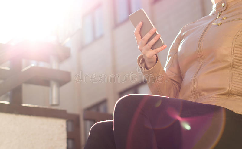Young urban woman messaging with smartphone in sunset or sunrise. Modern lifestyle. Stylish fashion girl chilling in city in sunshine with mobile device. Light stock photos