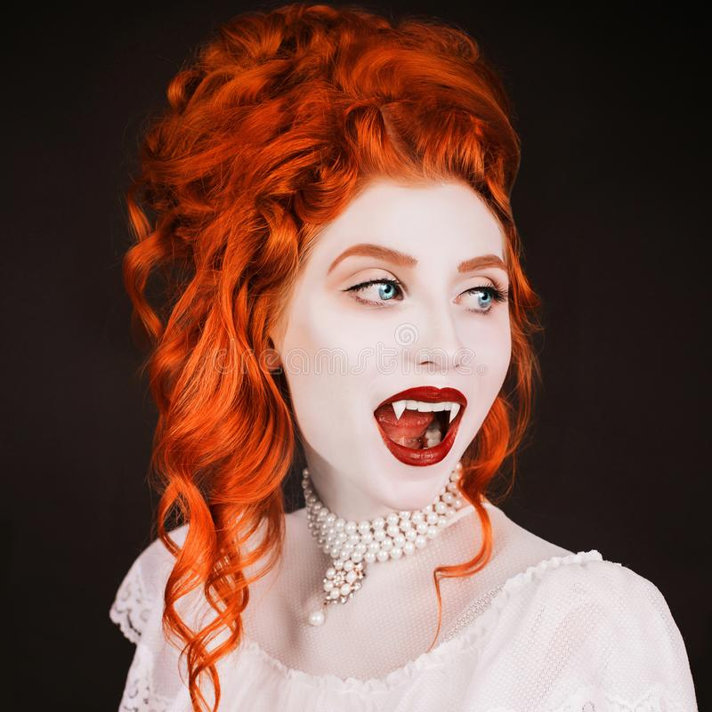 Young vampire woman with long curly hair, pale skin in a white dress on a black background. A beautiful redhead model with red lip stock photography