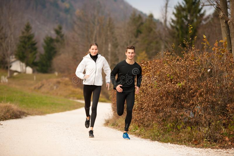 Young veautiful couple runs on a path in park on autumn afterno stock images