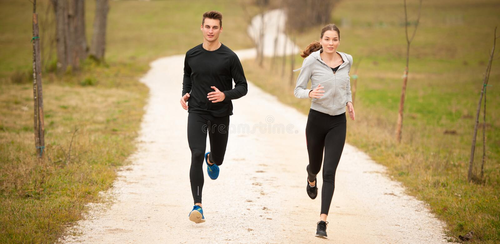 Young veautiful couple runs on a path in park on autumn afterno royalty free stock images