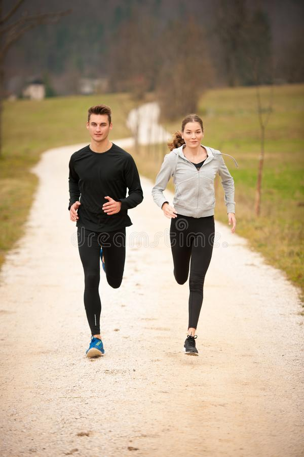 Young veautiful couple runs on a path in park on autumn afternoon stock image