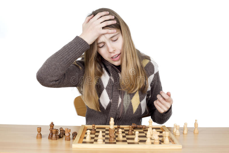 Young Very Disappointed Girl Slapping Hand On Head To Say Duh, Expressing Regret For Mistake She Made During The Chess Game royalty free stock photo