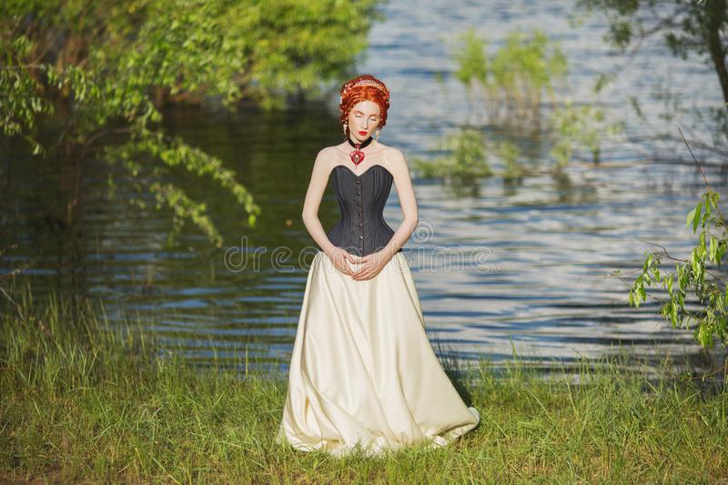 Young victorian princess with hairstyle on nature background. Rococo queen in white historic dress against backdrop of blue water. Doll in corset. Victorian stock image