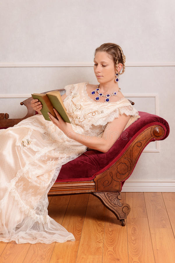 Young victorian woman reading book stock photo