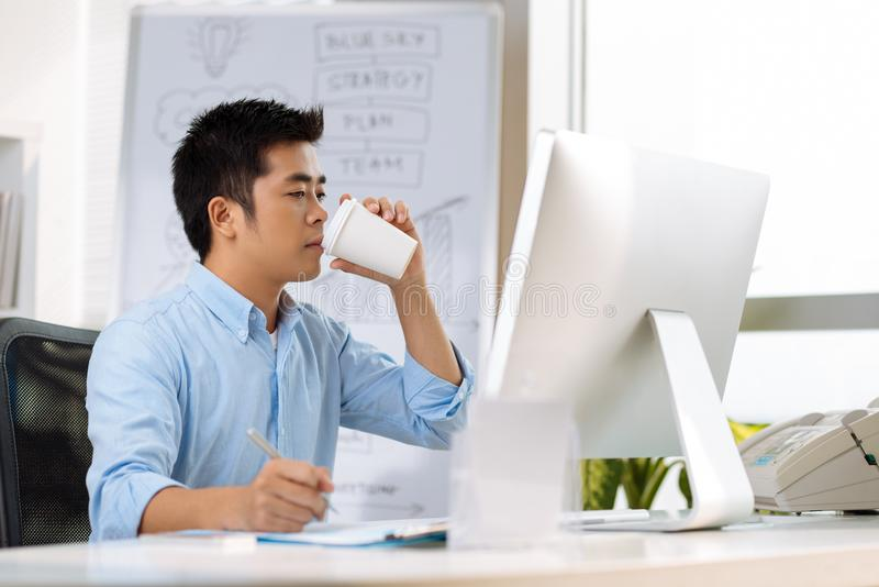 Project manager. Young Vietnamese entrepreneur drinking coffee and working on new project at his table royalty free stock photography