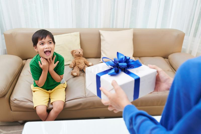 Excited birthday boy. Young Vietnamese men excited to accept birthday gift from his mother royalty free stock image