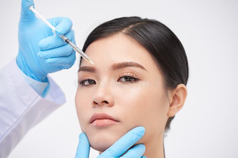 Beauty victim. Young Vietnamese women getting botox injection between her eyebrows stock photo