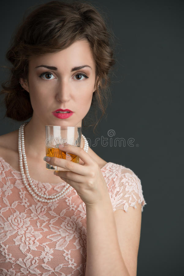 Young vintage woman holding a drink stock photo