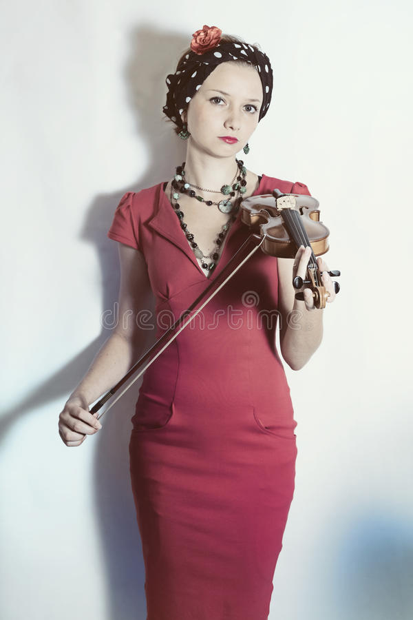 Young violinist woman with violin in hands. On a white background. Studio portrait stock photography