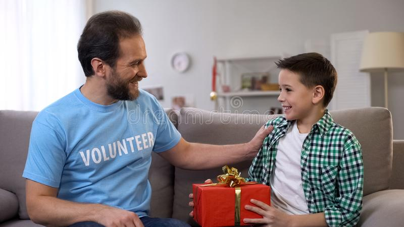 Young volunteer giving boy birthday present, social adaptation for orphans, care royalty free stock photos