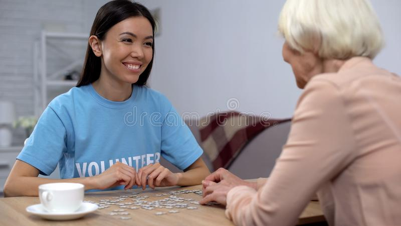 Young volunteer helping aged woman playing puzzle game in nursing home, care royalty free stock photos