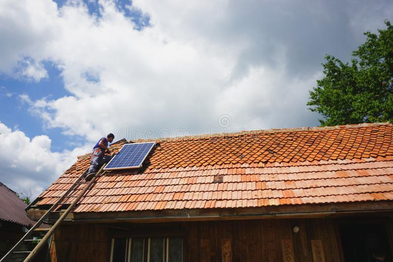 Young volunteer man up on a ladder, installing a photovoltaic solar panel on the roof of an old house stock photo