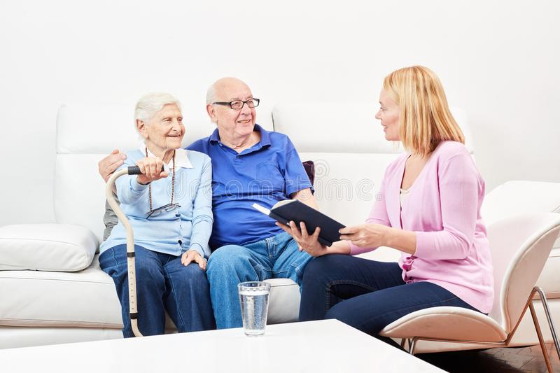 Woman from volunteer service reads seniors. Young volunteer women reads stories from a book to seniors stock photography