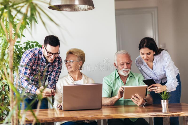 Volunteers help senior people on the computer. Young people giving senior people introduction to internet royalty free stock photos