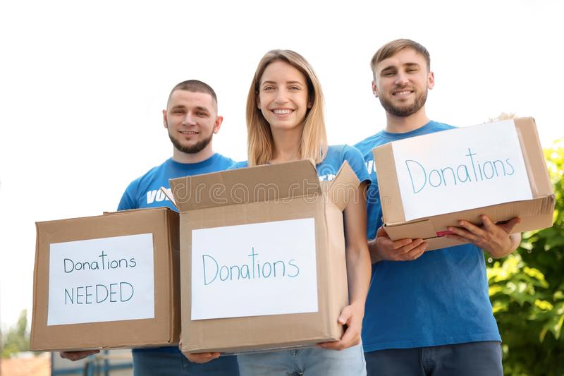Young volunteers holding boxes with donations. For poor people outdoors royalty free stock photography