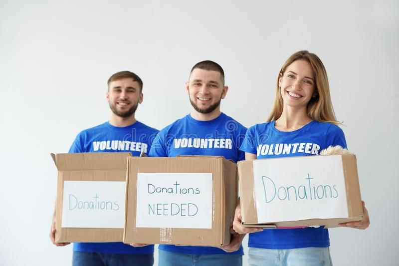 Young volunteers holding boxes with donations. For poor people on light background stock photography
