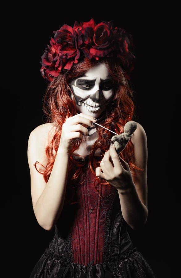 Young voodoo witch with calavera makeup (sugar skull) piercing doll. Young voodoo witch with calavera makeup (sugar skull) piercing a doll stock images