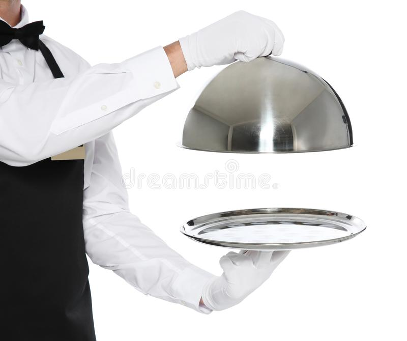 Young waiter holding metal tray with lid. On white background royalty free stock photo