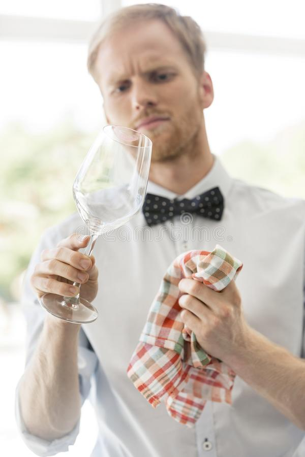 Young waiter looking while cleaning wineglass at restaurant royalty free stock photos