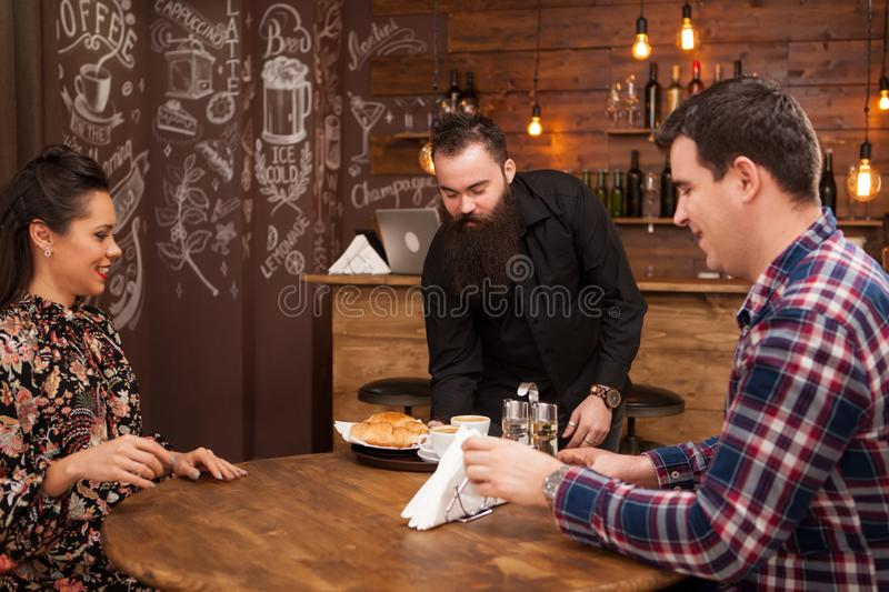 Young waiter serving food to male and female customers at table in cafe royalty free stock images