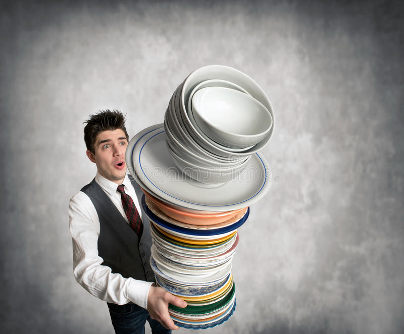 Young waiter with a stack of plates in hand stock photography
