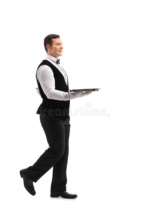 Young waiter walking with an empty tray royalty free stock photo