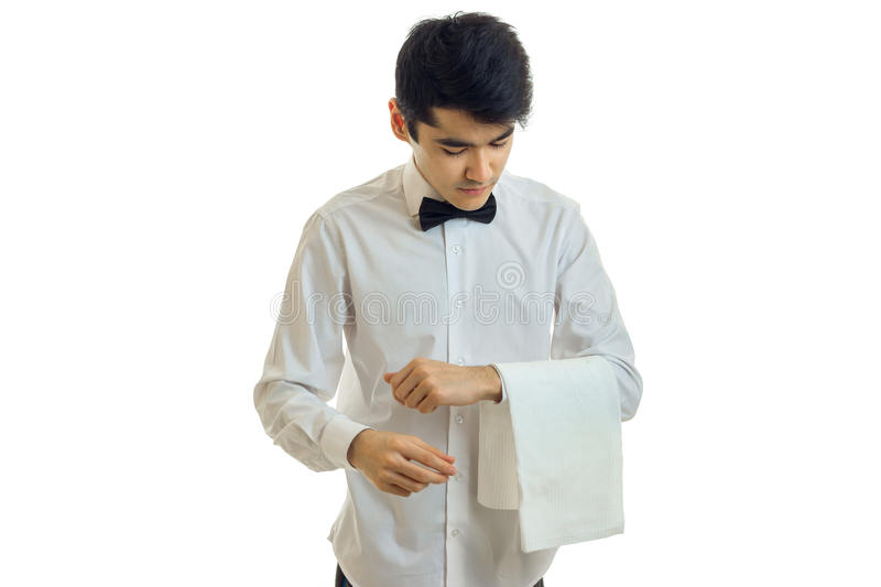 A young waiter in a white shirt tilted his head and keeps on hand a towel stock photo