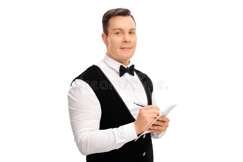 Young waiter writing an order in a notepad royalty free stock photography