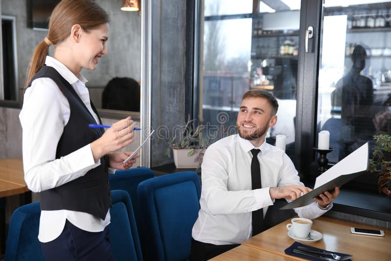 Young waitress taking an order from man in restaurant stock photos