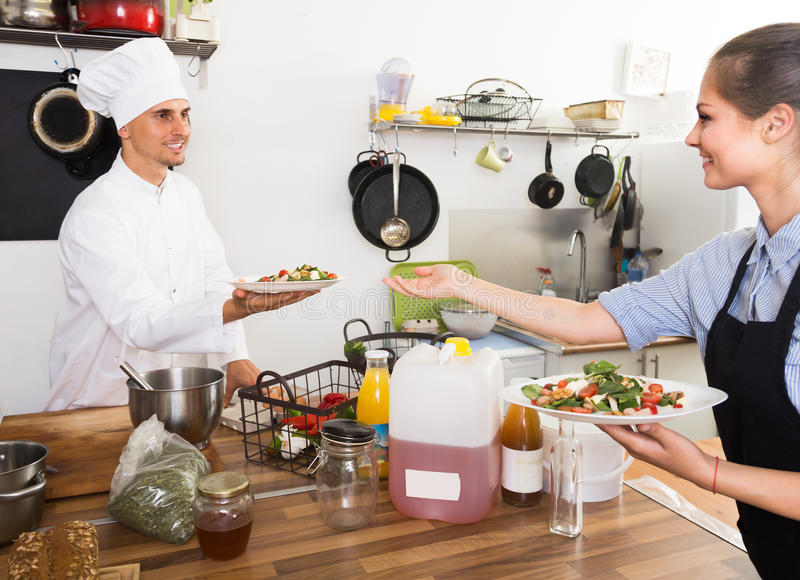 Young waitress taking served salad from chef royalty free stock photos
