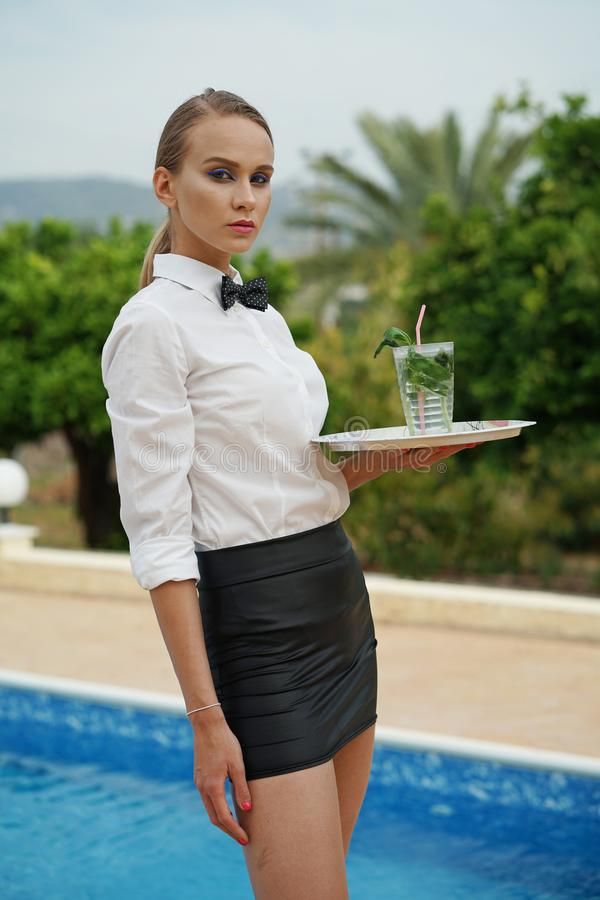 Waitress with tray and drink outdoors royalty free stock photography