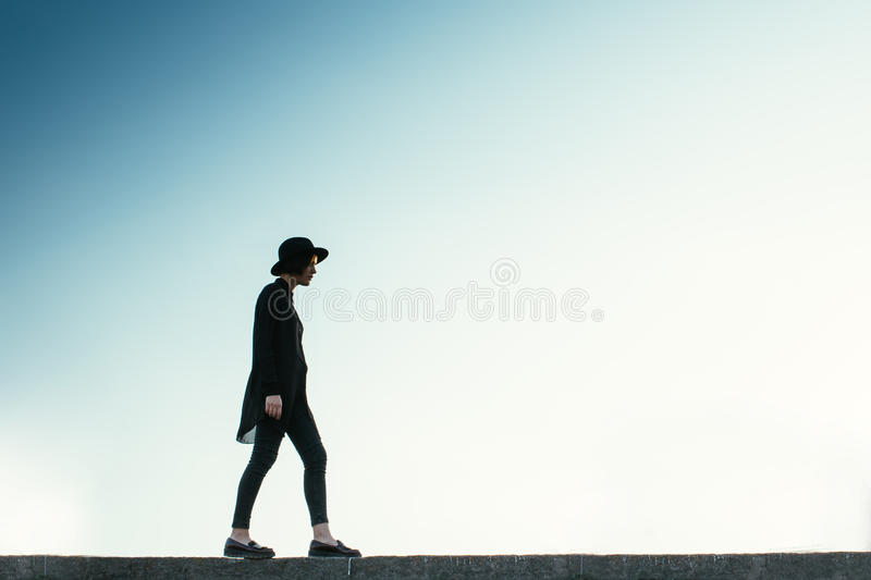 Young walker. Silhouette of a slender girl against the sky royalty free stock images