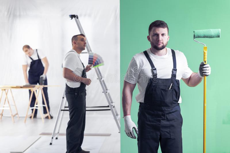 Young wall painter posing with a roller on a green wall background, a decorator choosing colors and a carpenter cutting in blurry stock image