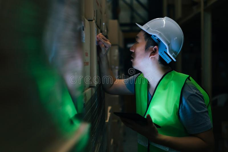 Worker with safety hat checking order details with tablet at inventory room stock image