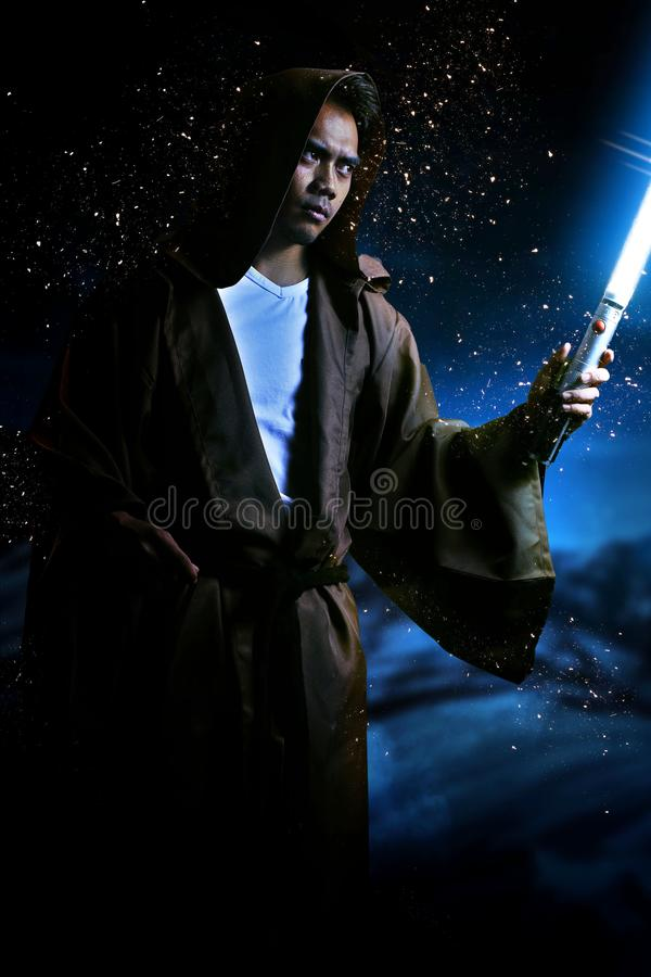 Young warrior with brown hooded cape holding a light saber. During the night royalty free stock images