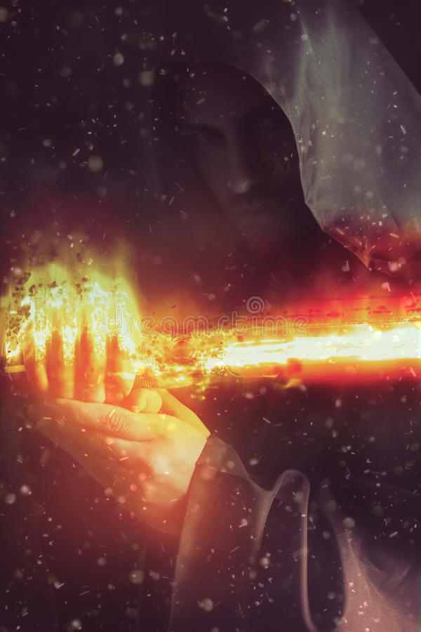Young warrior holding a saber in fire. Young warrior wearing a hood holding a burning saber royalty free stock image