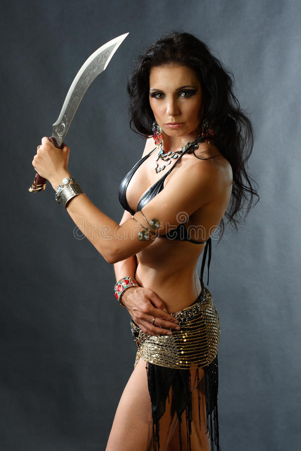 Young warrior woman. Studio shot of young warrior woman holding sword in her hand stock photos