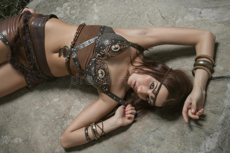 Young warrior woman. Young beautiful woman dressed in a leather wear looking like an amazon or warrior lying on a big stone. Dramatic beauty shot stock images
