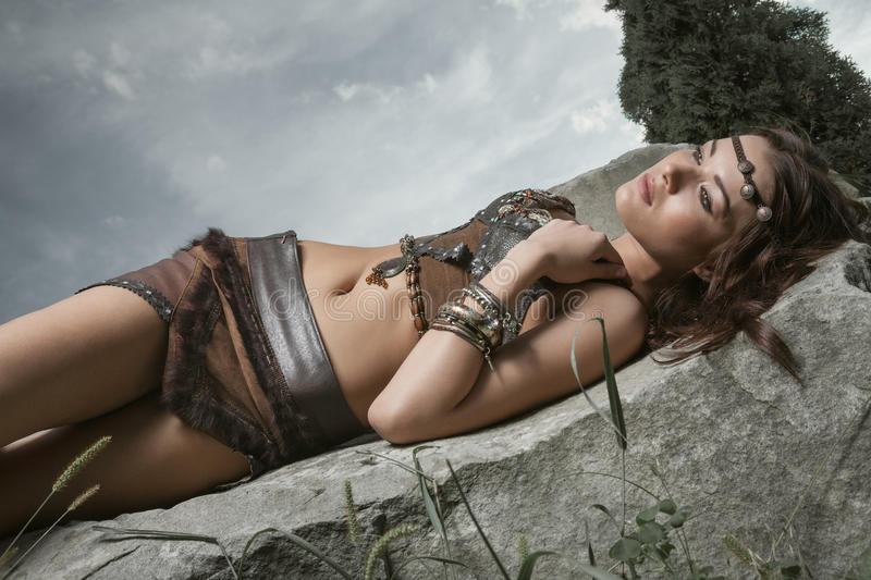 Young warrior woman. Young beautiful woman dressed in a leather wear looking like an amazon or warrior lying on a big stone. Dramatic beauty shot royalty free stock photography