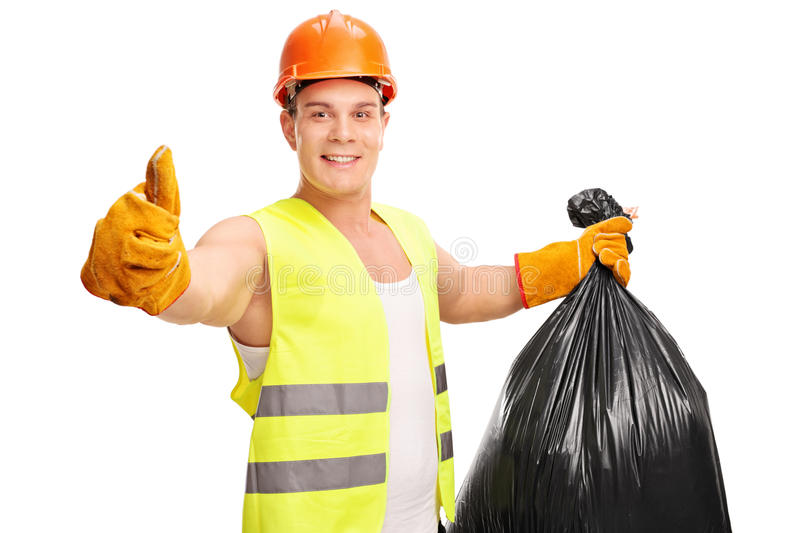 Young waste collector holding a trash bag. Young male waste collector holding a trash bag and giving a thumb up isolated on white background royalty free stock image