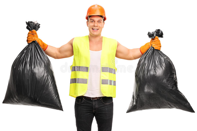 Young waste collector holding two trash bags. Young cheerful waste collector holding two trash bags and looking at the camera isolated on white background royalty free stock photo