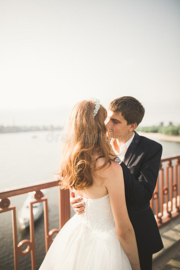 Young wedding couple, beautiful bride with groom portrait on the bridge, summer nature outdoor royalty free stock photos