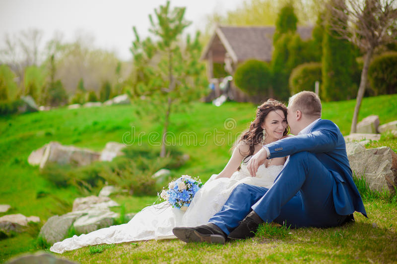 Young wedding couple enjoying romantic moments outside on a summer meadow royalty free stock photography