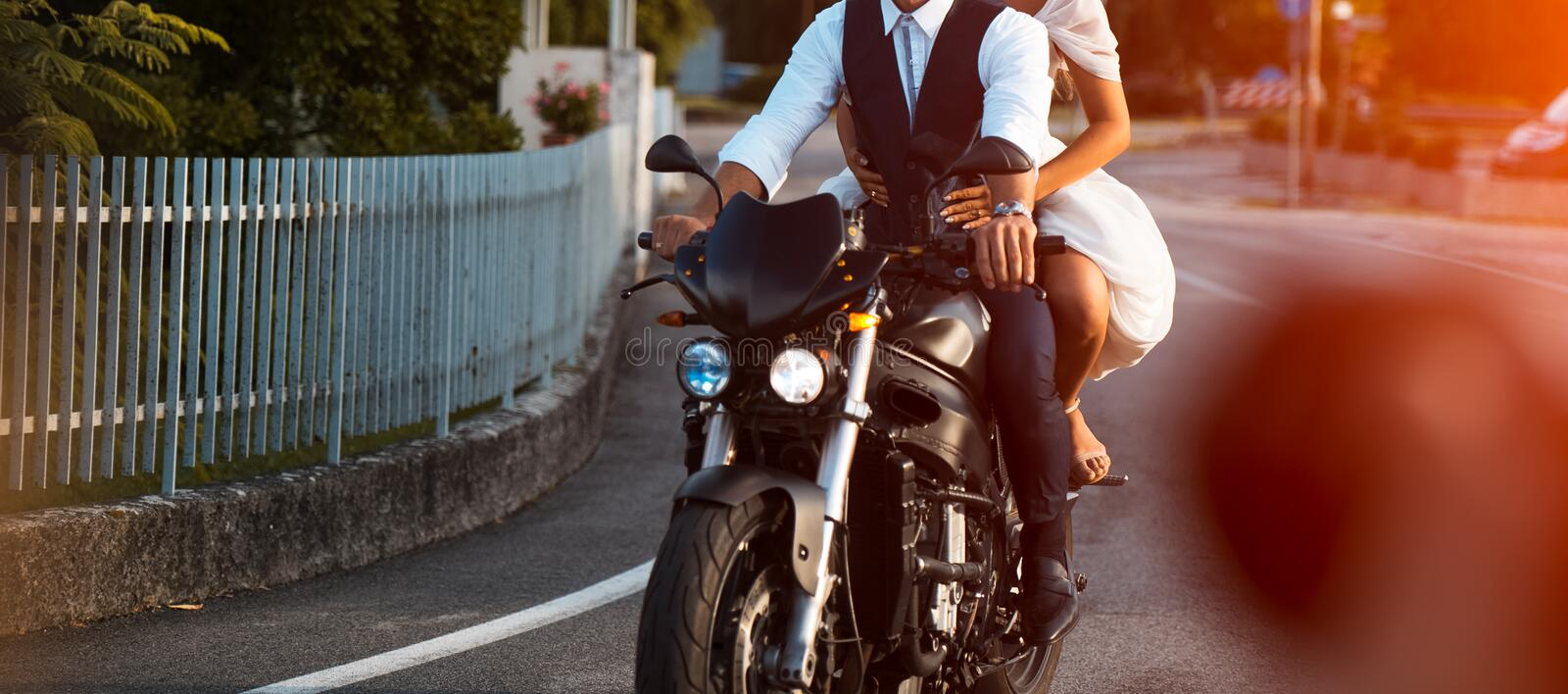 Young wedding couple riding black motorcycle in the city stock photography
